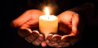 Brennende Kerze in Händen